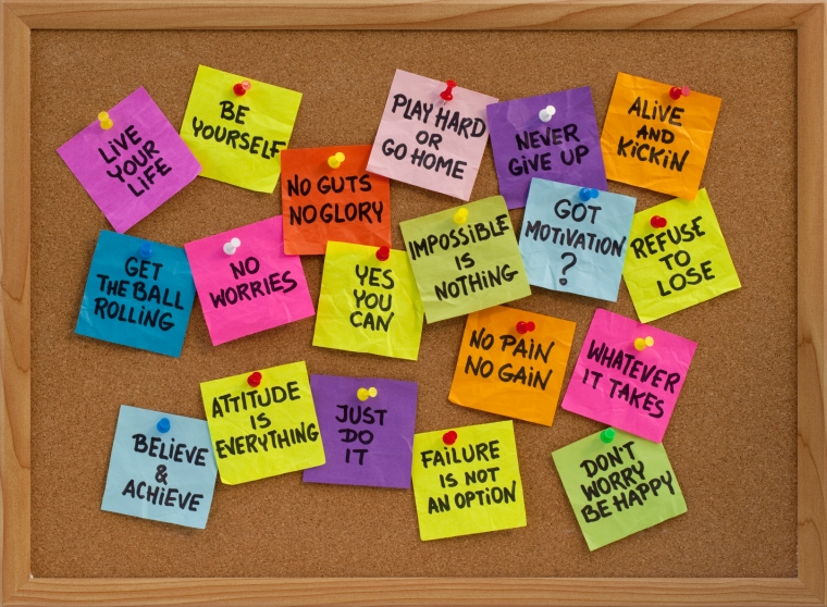 motivational slogans and phrases - colorful reminder notes with handwriting on cork bulletin board